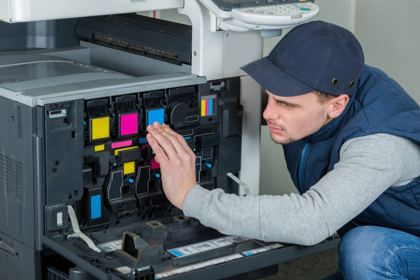 technician repairing digital photocopier printer machine